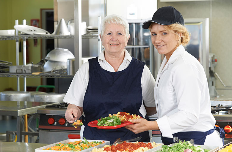 Two women serving food